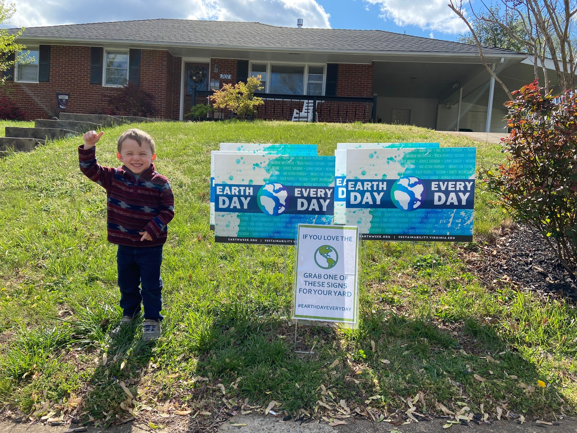Small child standing next to EDED lawn signs in his front yard