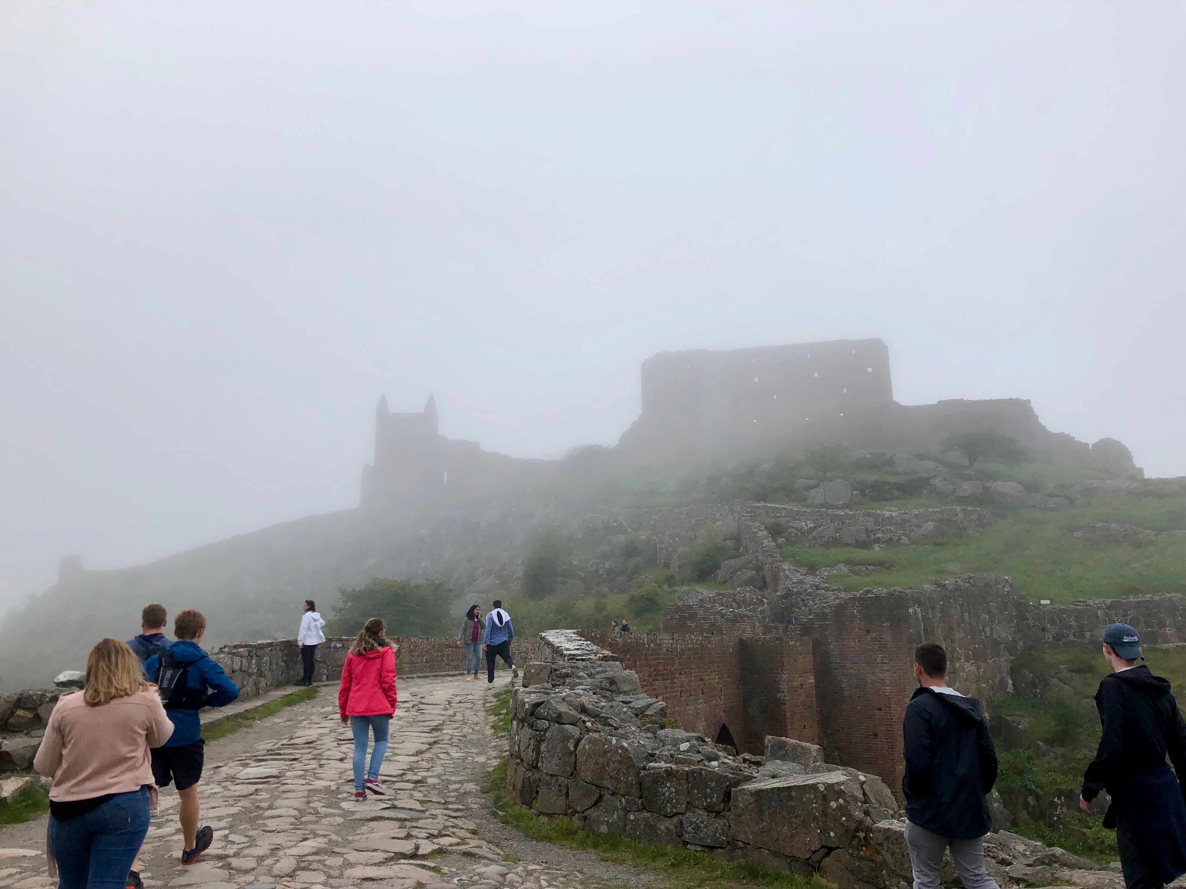 Students approaching castle ruins on a foggy day.