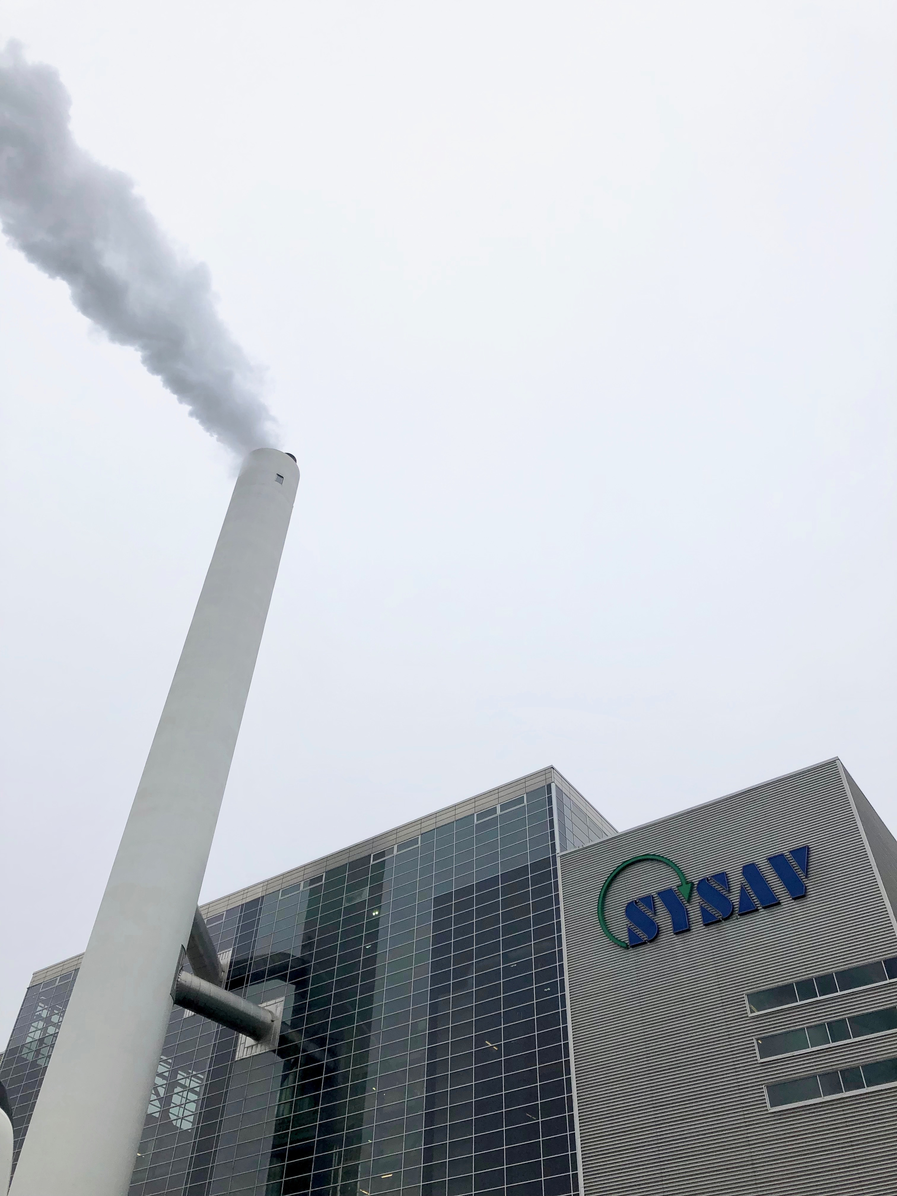 Exterior of waste-to-energy plant with prevalent smoke stack.