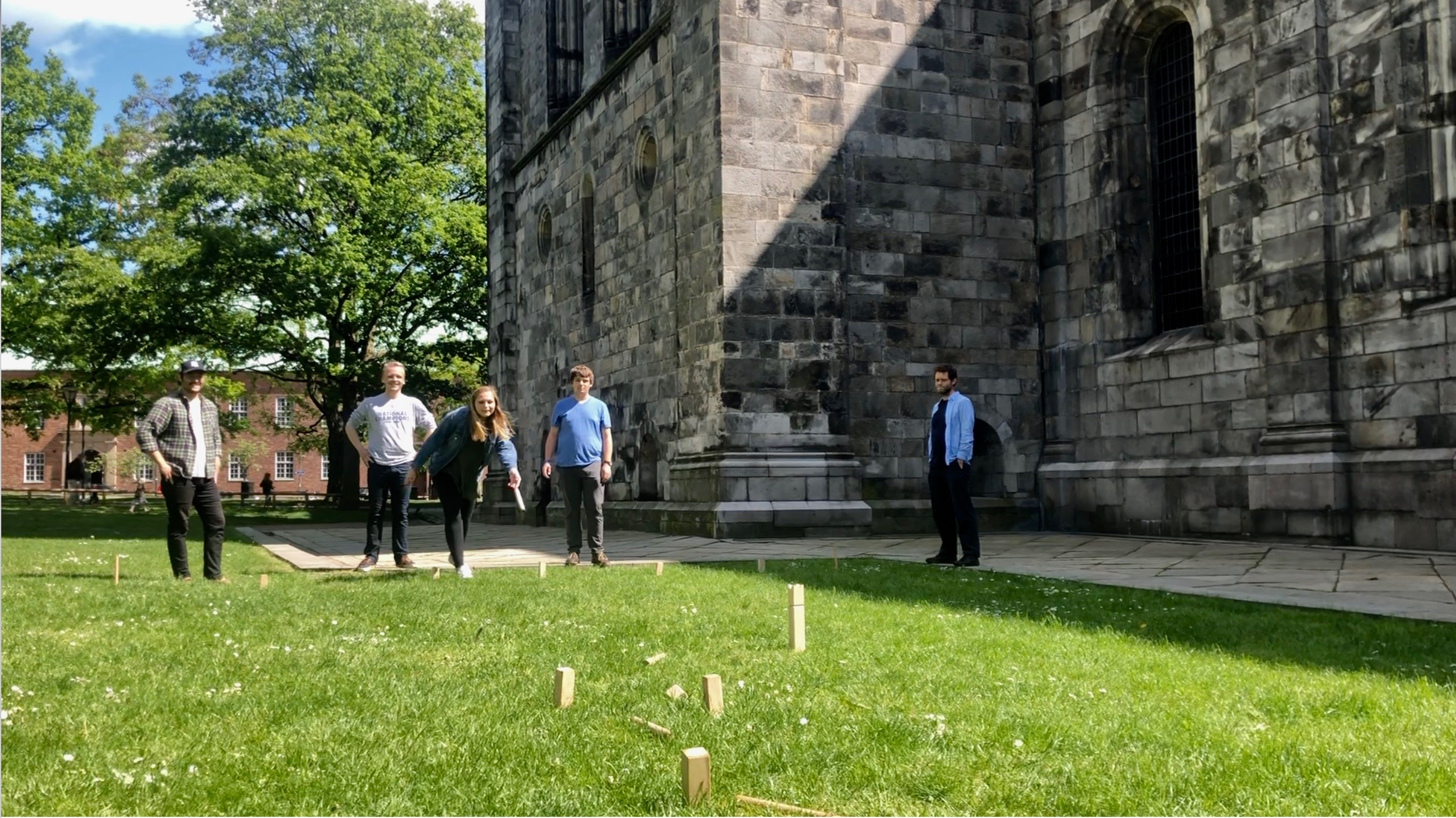 A professor and his students play kubb, with wooden blocks, in the grass.