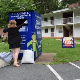 A student donating gently used items to a Goodwill donation box on Grounds for Hoos ReUse.