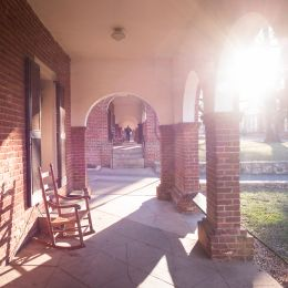 Sunlight shining through the archways next to a Lawn Room with a rocking chair facing the Lawn