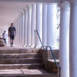 Students walking through the colonades near the Lawn
