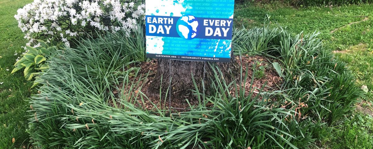 Earth Day Every Day yard sign in front of a tree with flower landscaping.