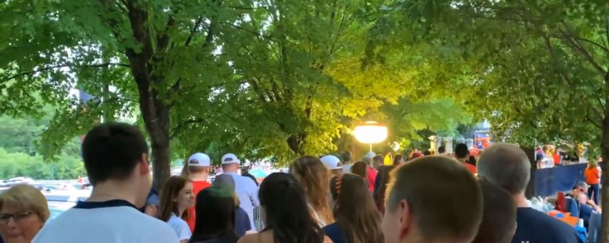 A crowd of people walking by Scott Stadium before the UVA Green Game
