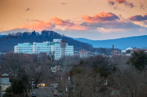 View of the sunset over the hospital with mountains and trees