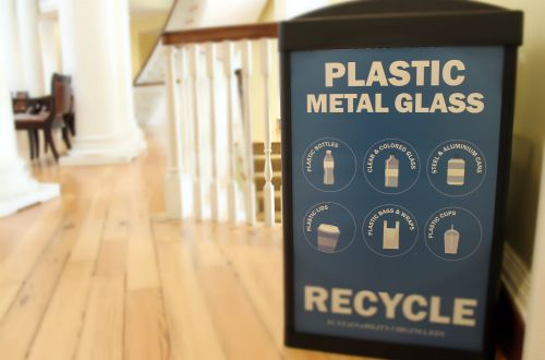 "Photo of a blue and black recycling container that reads "" Plastic, Metal, Glass, Recycle"""