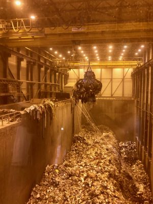 Inside of waste-to-energy plant with large pit of trash.