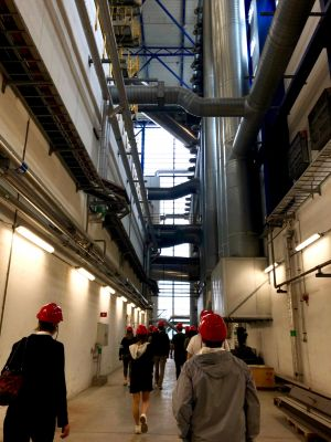 Students tour of interior of waste-to-energy plant, wearing red hard hats.